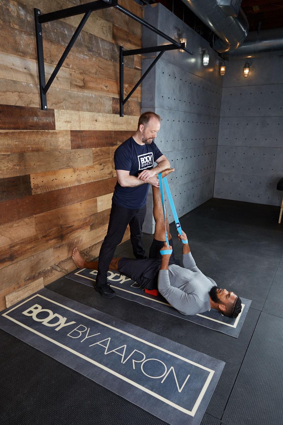 Coaching Stretching Man on Floor